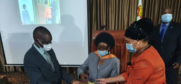 Dr Stembiso G G Nyoni(MP) cutting the ribbon flanked by Hon Soda Zhemu(Left) and Hon J N Mhlanga(Right)
